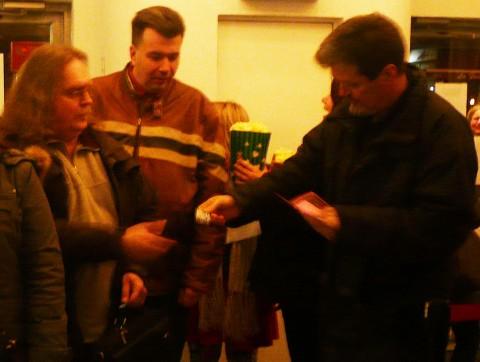 Walter Duralija on the right handing a ticket to James Waley with Scott VanderPloeg watching on.