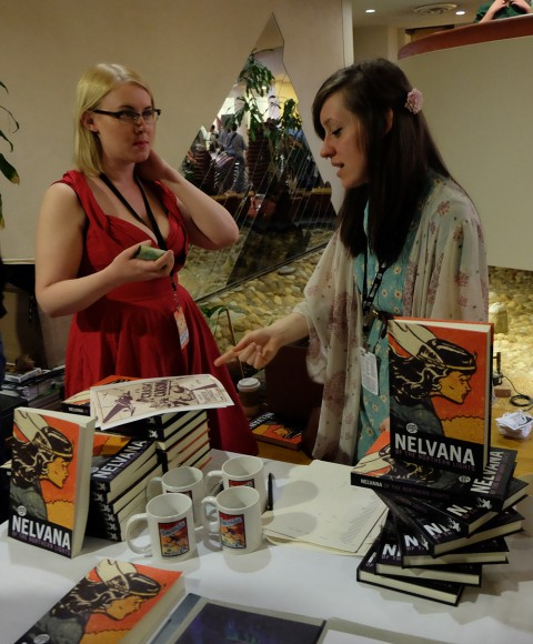 Rachel Richey admires her Jack Tremblay signed page while Hope Nicholson looks on at their Nelvana reprint book table.